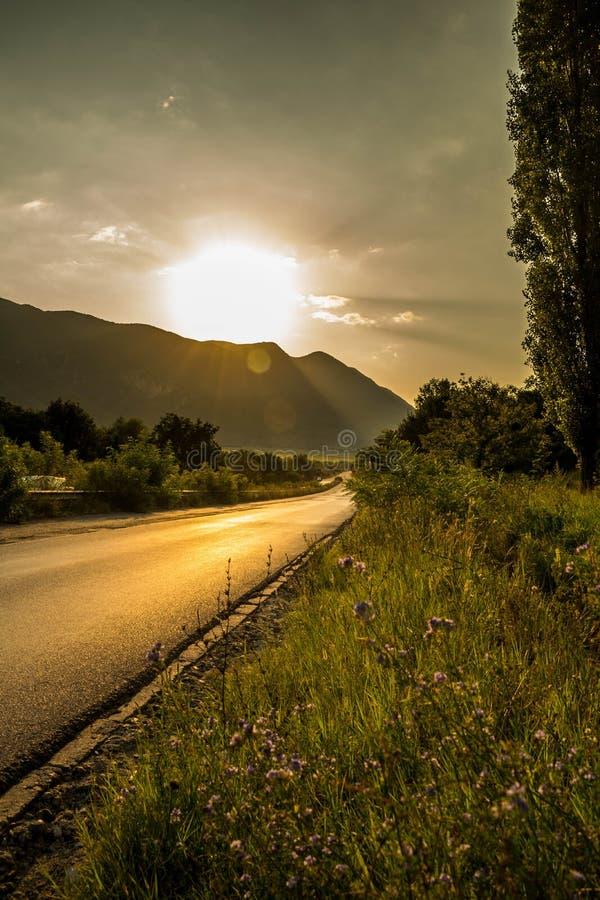 Solnedgång över vägen nära bergen royaltyfri bild