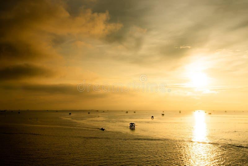 Solnedgång över vattnet med molnig himmel royaltyfri foto