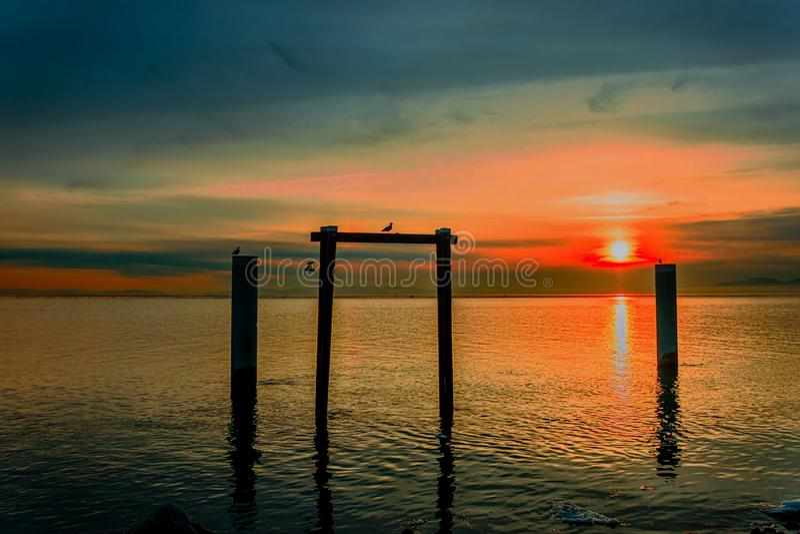 Solnedgång av vintersolen över havet, reflexion i vattnet royaltyfri foto