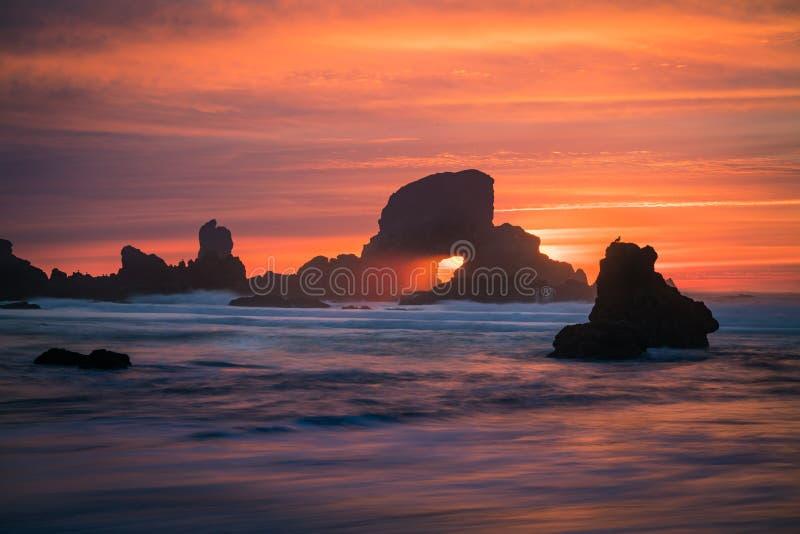 Solnedgång bak båge på den Oregon kusten USA arkivfoton