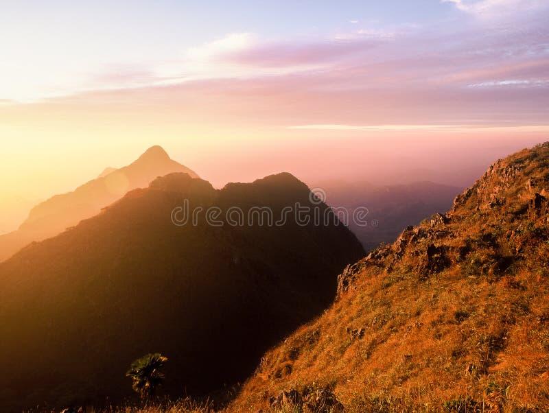 Solnedgång bak berg royaltyfria foton