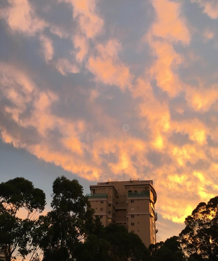 Solnedgång bak byggnaden i staden fotografering för bildbyråer