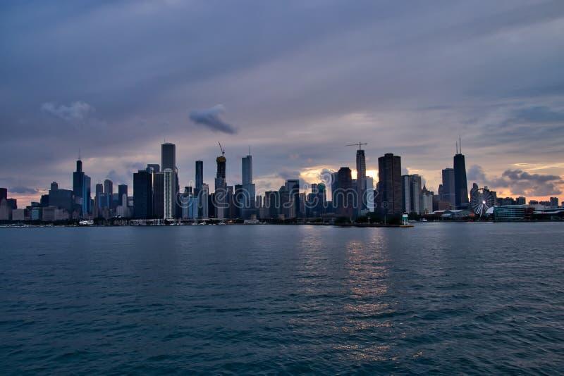 Solnedgång bak Chicago horisont, med reflexion av ljus och byggnader på vattnet av Lake Michigan royaltyfria bilder