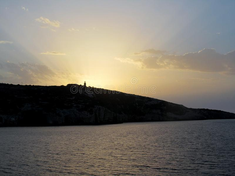 Solnedgång bak en fyr i Zakynthos arkivbilder