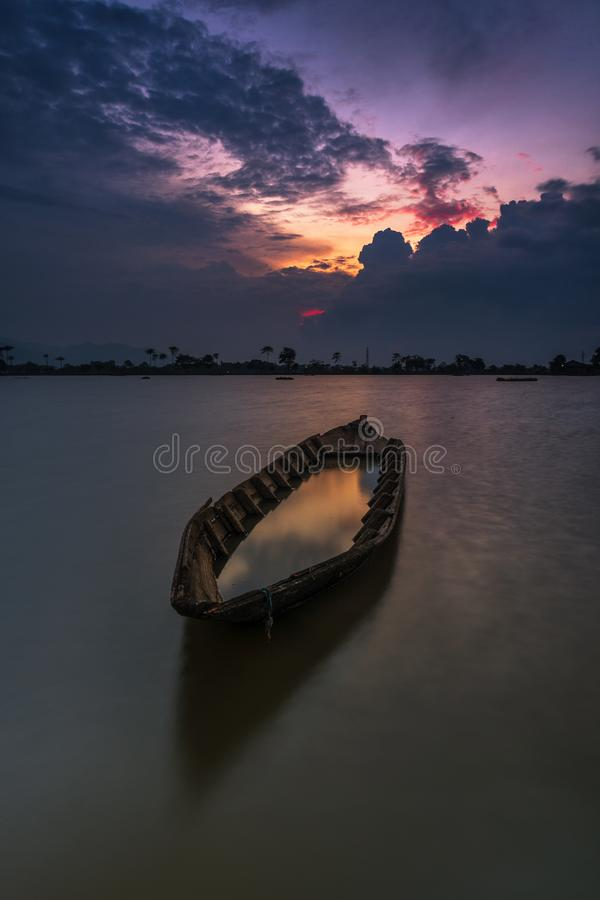 Solnedgång bak fartyget i mitt av risfält royaltyfri fotografi