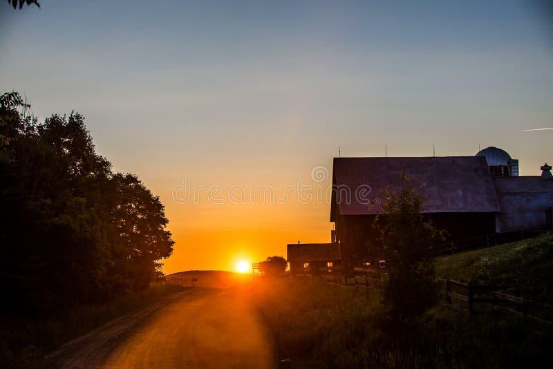 Solnedgång bak gammal ladugård royaltyfri foto