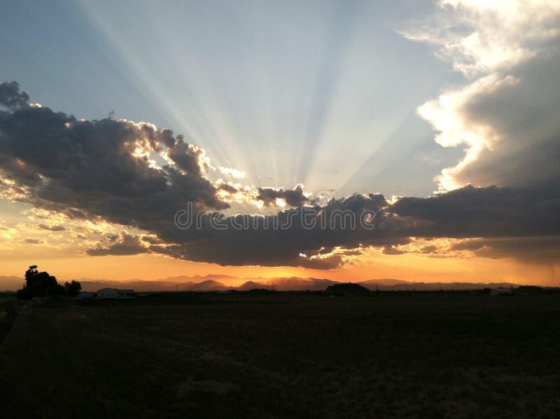 Solnedgång bak moln över berg arkivbilder