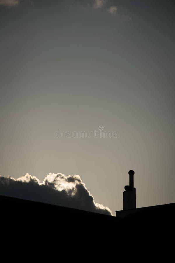 Solnedgång bak moln i staden arkivbild