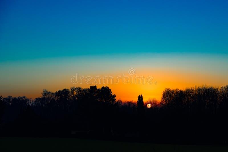 Solnedgång bak träd, storartad aftonhimmel med den orange solbollen bak kala träd Gyllene regler fotografering för bildbyråer