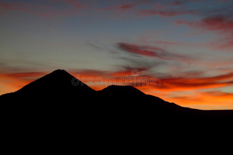 Solnedgång bak vulkanbergkonturn royaltyfri bild