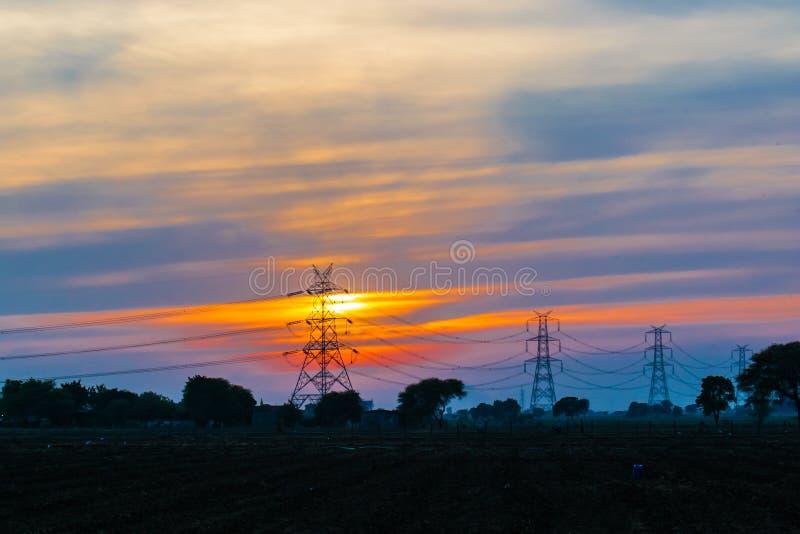 Solnedgång, blå himmel och elektricitetstorn royaltyfria bilder