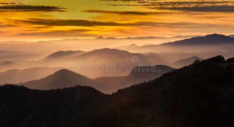 Solnedgång, dimmiga dalar och bergskedjor arkivbild