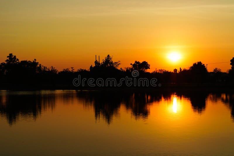 Solnedgång eller solnedgång på floden arkivbild
