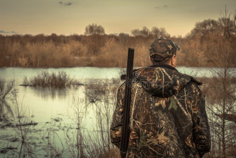 Solnedgång för bakre sikt för säsong för jakt för flod för flod för kamouflage för jägaremanhagelgevär undersökande arkivbilder