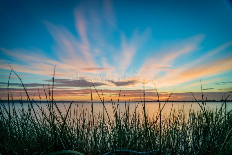 Solnedgång för blå himmel och apelsinöver en sjö i Australien royaltyfri foto