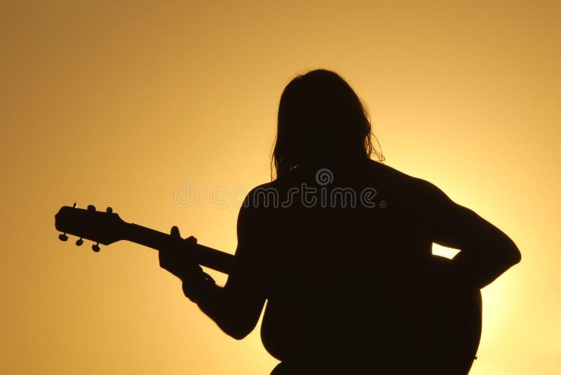 solnedgång för gitarrmansilhouette arkivbild