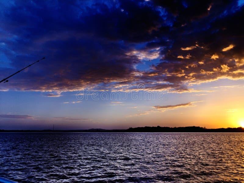 Solnedgång för guld- glöd över vatten med reflexioner arkivfoto