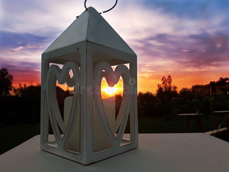 Solnedgång för hållare för stearinljus för förälskelsehjärtasymboler fotografering för bildbyråer