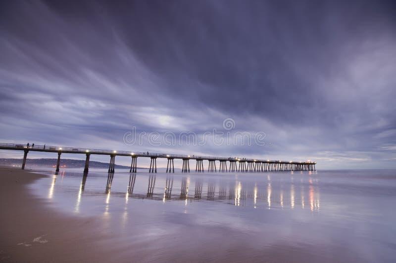 Solnedgång för Hermosa strandpir arkivfoto