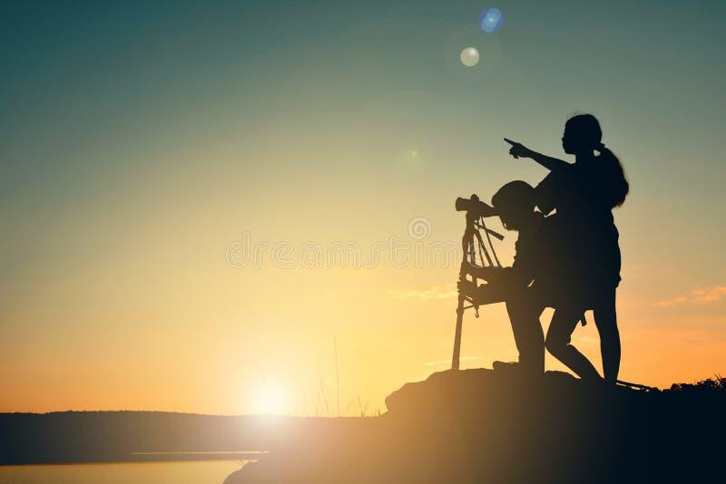 Solnedgång för konturkvinna- och flickaskytte på det bästa berget royaltyfria foton