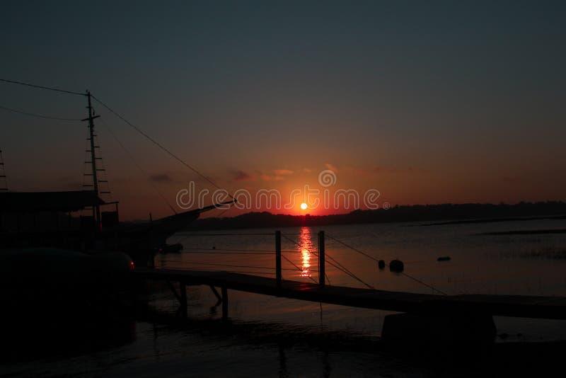 Solnedgång, fartyg, färger, fred och natur arkivfoto