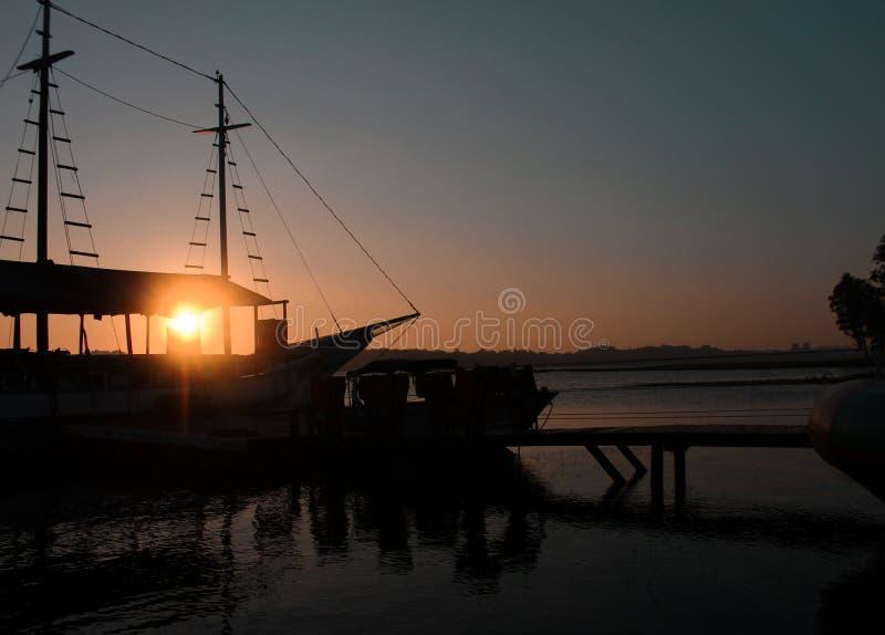 Solnedgång, fartyg, färger, fred och natur royaltyfria foton