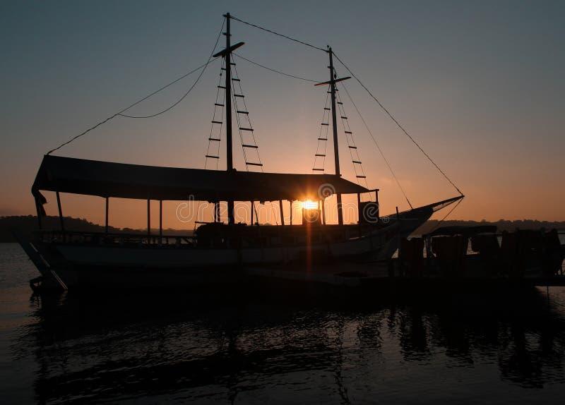 Solnedgång, fartyg, färger, fred och natur arkivfoton