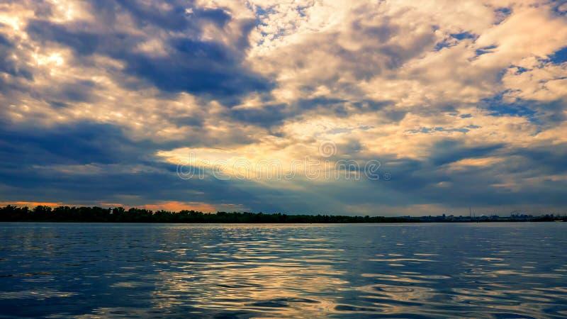 solnedgång framme av en åskväder, på horisonten av floden arkivfoton