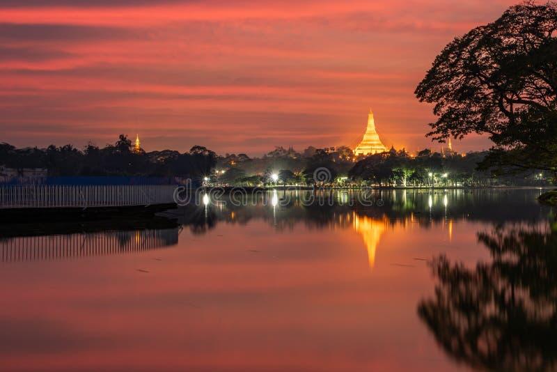 Solnedgång framtill av sjön, sikt av den Shwedagon pagoden, Yangon, Myanmar Burma Asien Buddhapagod arkivfoto