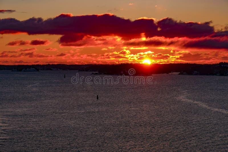 Solnedgång Guld- himmel för rubin över havet royaltyfri foto