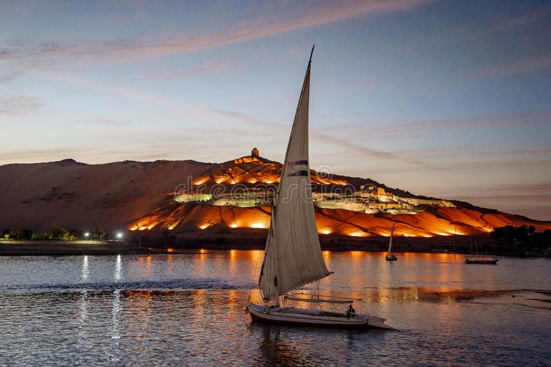 Solnedgång i Aswan Egypten med det Felucca fartyget på Nilet River royaltyfri bild