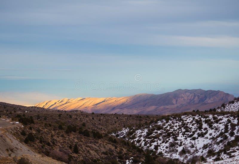 Solnedgång i berg arkivfoto