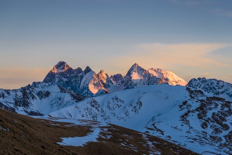 Solnedgång i bergen Snö-korkade berg exponeras av det orange ljuset av inställningssolen arkivfoto