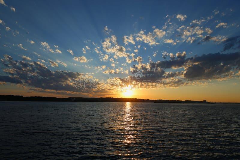 Solnedgång i den New York hamnen arkivbilder