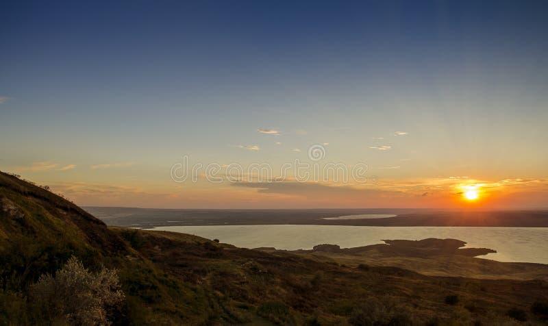 Solnedgång i det guld- solljuset över en bergsjö royaltyfri fotografi