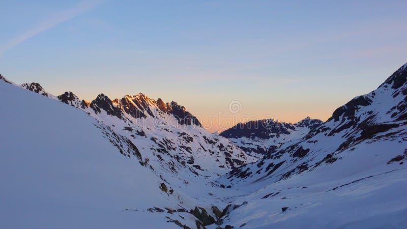 Solnedgång i ett vinterberglandskap i den Silvretta bergskedjan i de schweiziska fjällängarna royaltyfri foto