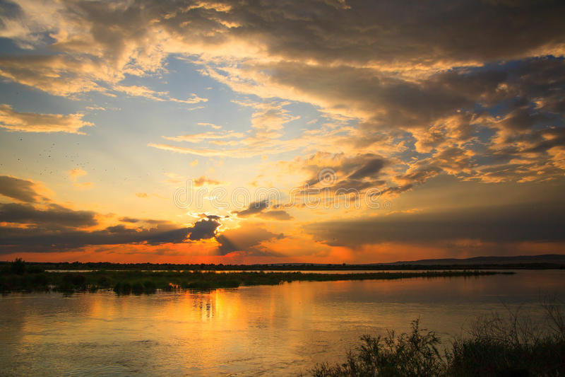 Solnedgång i floden med reflex arkivfoto