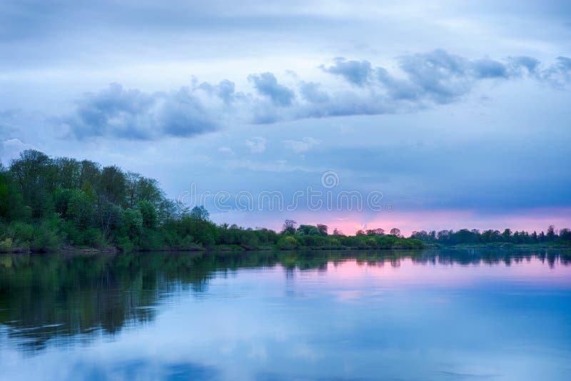 Solnedgång i floden med reflex arkivbild