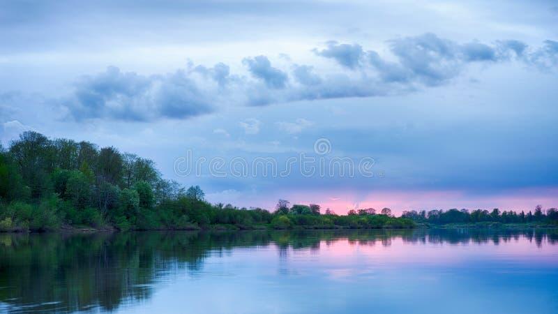 Solnedgång i floden med reflex royaltyfria bilder