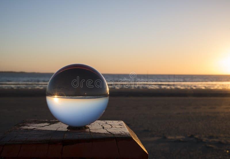 Solnedgång i glass shpere på stranden fotografering för bildbyråer