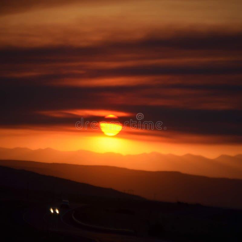 Solnedgång i min rearview arkivbild