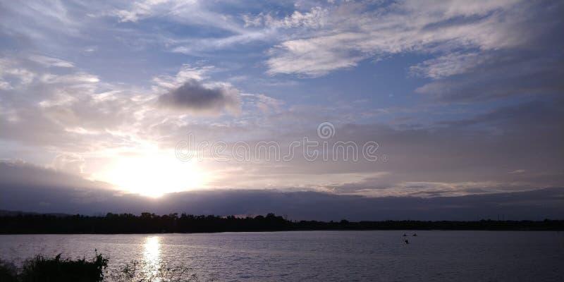 Solnedgång i moln i sjösikt arkivbild
