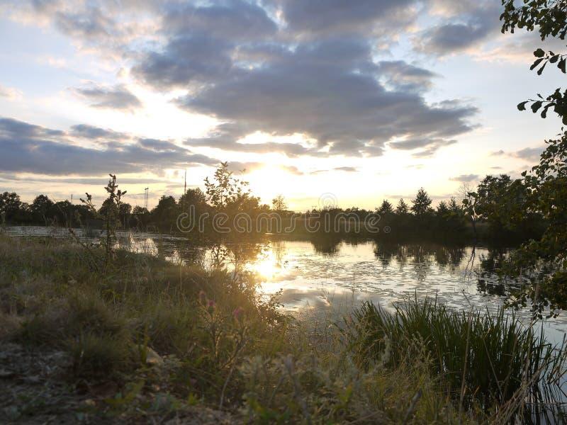 Solnedgång i naturen, floden, kusten i gräsplanen, moln arkivfoton