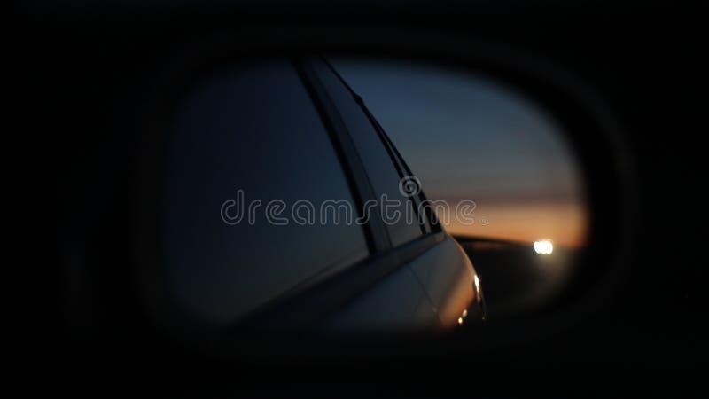 Solnedgång i spegeln av bilen royaltyfri bild