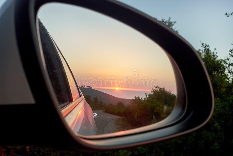 Solnedgång i spegeln av bilen och havet royaltyfri fotografi