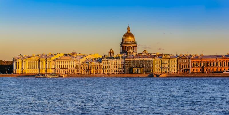 Solnedgång i St Petersburg över den Neva floden med sikten av slottinvallningen och helgonet Isaac& x27; s-domkyrka royaltyfri fotografi