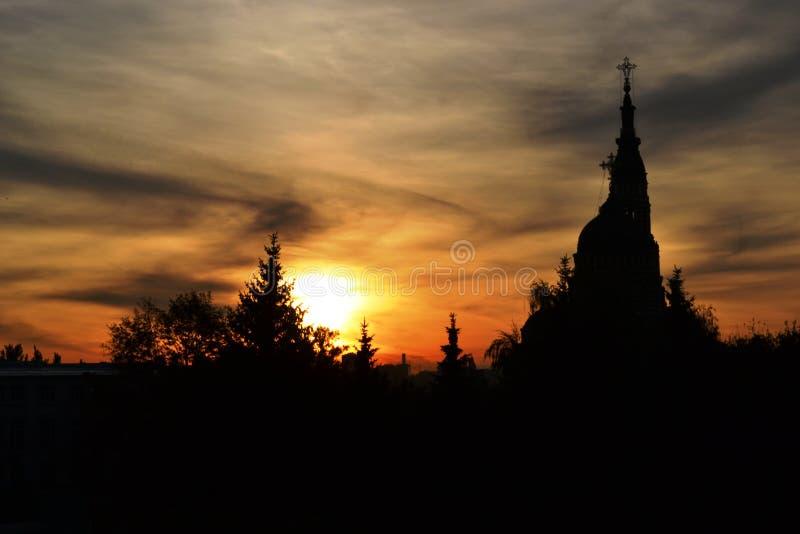 Solnedgång i staden, med mörka träd och en church2 royaltyfria foton