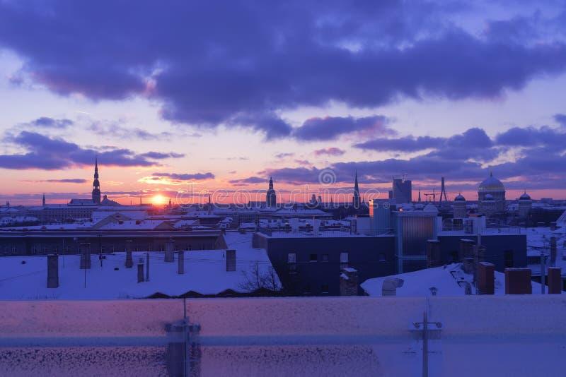 Solnedgång i vinter över staden av Riga arkivbild