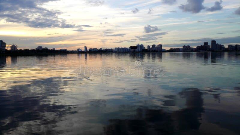 Solnedgång landskap, sikt av staden från vattnet arkivfoton