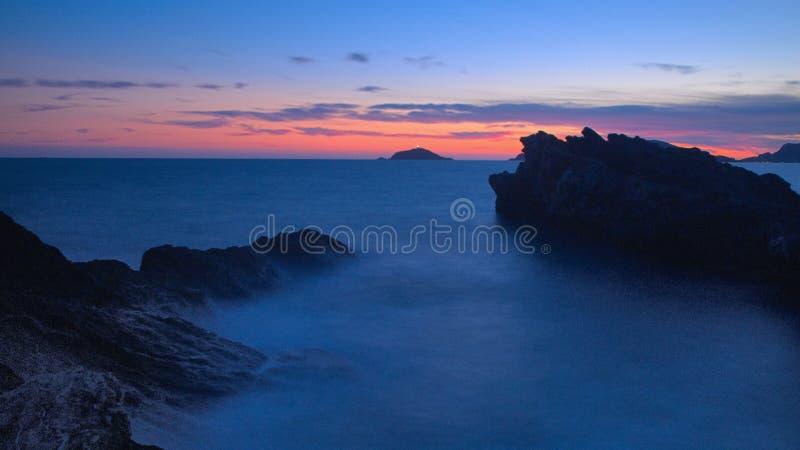 Solnedgång med ön royaltyfria bilder